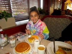 Young guest enjoying breakfast at Omega Restaurant & Pancake House in Downers Grove