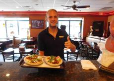 Friendly manager serving tacos at Brandy's Gyros in Hanover Park