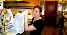 Friendly staff with carryout order at Charcoal Flame Grill in Morton Grove