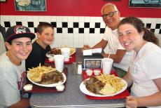 Family feasting on hearty gyros plates at Plush Pup Gyros Restaurant in Norwood Park